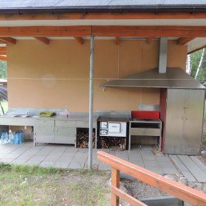 przy sanitariatach: zlewozmywak z kuchennym stołem roboczym, grillem, suszarnio-wędzarnią i kuchnią